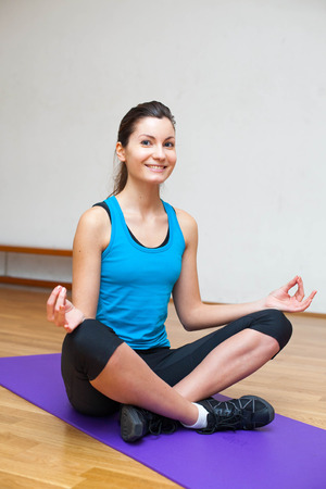 Picture of a smiling girl sitting in lotus pose Stock Photo