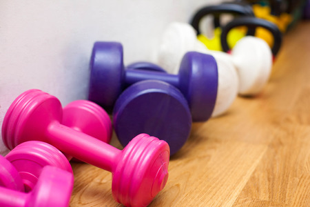 Picture of colorful dumbbells on the floor in the gym Stock Photo