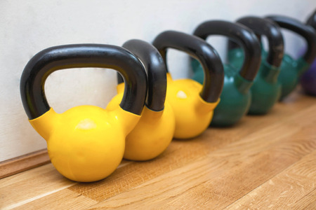 Colorful kettle bells on the floor in the gym photo