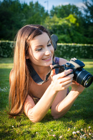Smiling girl with the camera in the park photo