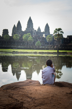Picture of a little boy looking at Angkor Wat temple in Cambodia