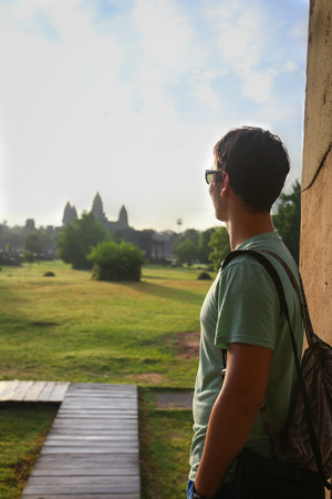 Picture of a tourist looking at Angkor Watt temple in Cambodia