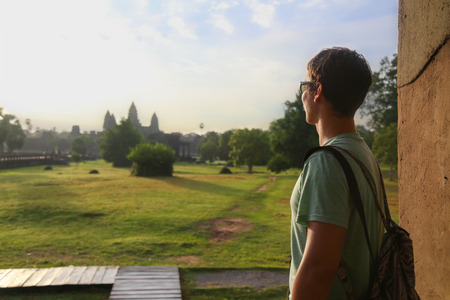Picture of a tourist looking at Angkor Wat temple in Cambodia
