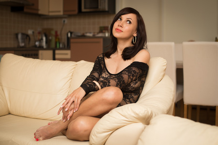 Beautiful woman sitting at home on the sofa