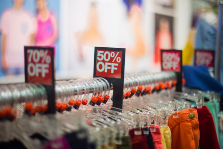 Sale on clothes in the retail store Stock Photo