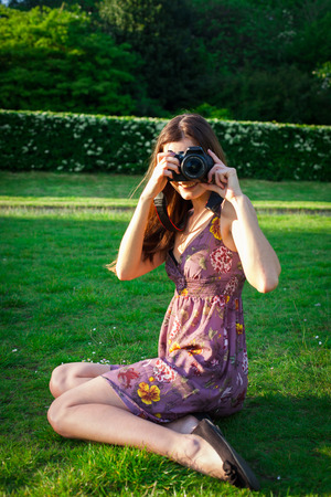 Girl with the camera in the park smiling and looking happy Stock Photo