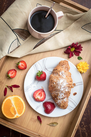 Coffee, croissant and fruits on the tray