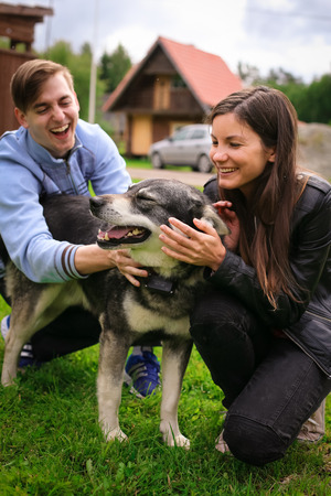Young people playing with a dog Stock Photo