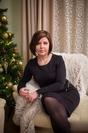 Young woman sitting on the sofa near the christmas tree