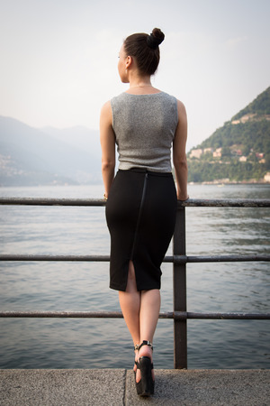 Young beautiful woman standing looking at the lake Stock Photo
