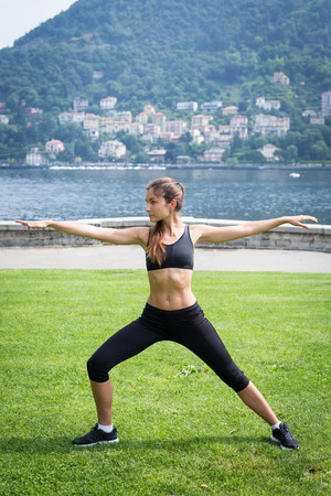 Young attractive woman doing exercises outdoors near the lake