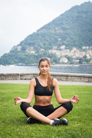 Young attractive woman meditating on the grass outdoors near the lake