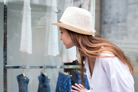 Young woman looking at the clothes through the shop window