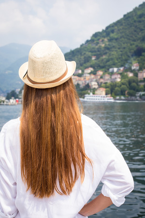Young woman with red hair looking at the beautiful view of the lake Como