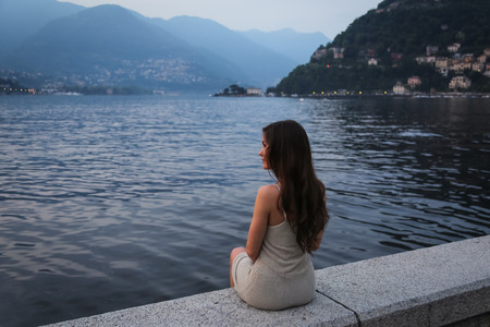 The young woman looking at the beautiful view at the lake Stock Photo