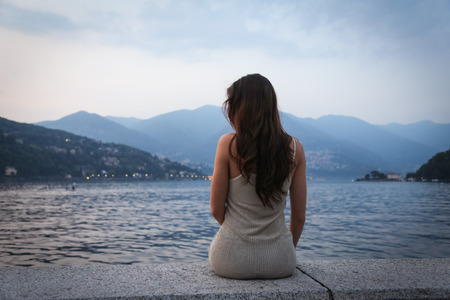The young woman looking at the beautiful view at the lake 스톡 콘텐츠
