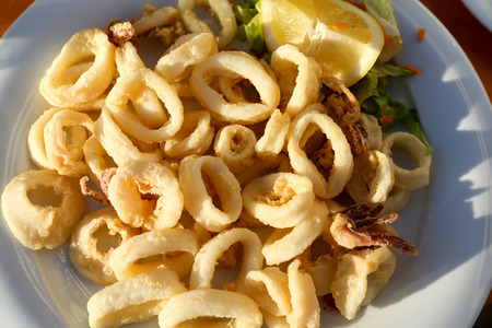 Fried calamari rings with lemon on the plate natural light