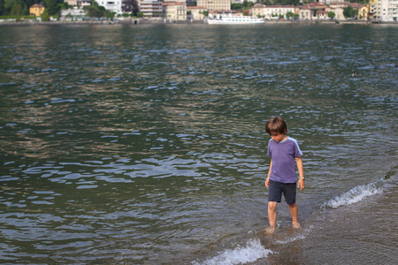Little boy walking along the water front at the lake looking thoughtful Stock Photo