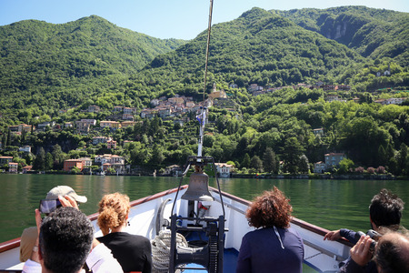 Tourists on the boat tour on the lake Como looking at the beautiful views