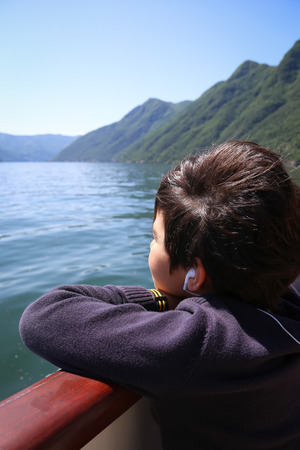 Little boy on the boat tour looking at the views at the lake Como