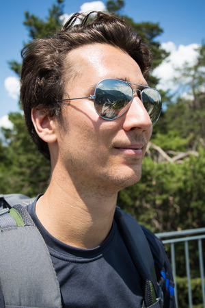 Portrait of a young traveller looking at the mountains with reflection in his sunglasses Stock Photo