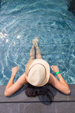 View from the top of a girl in a hat relaxing in the swimming pool Stock Photo