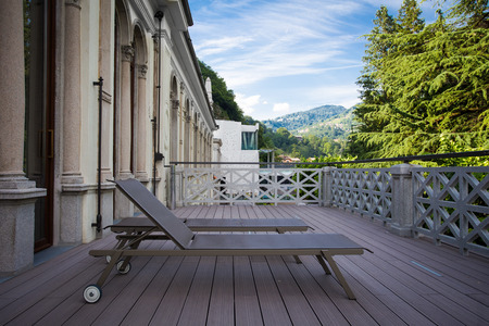 Sunbeds on the balcony with beautiful view of the mountains on the background and blue sky