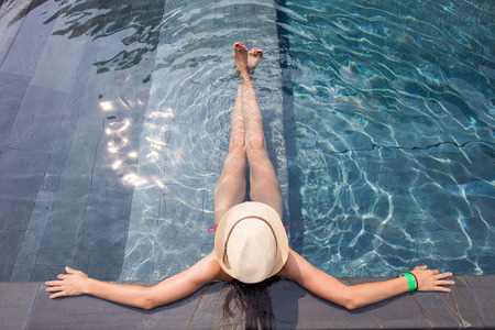 floating: View from the top of a girl in a hat relaxing in the swimming pool Stock Photo