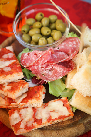Delicious food platter with salami, bread, pizza and olives