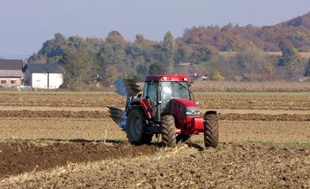 ploughing: Framer ploughing with the tractor on the autumn fields.