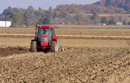 framer: Framer ploughing with the tractor on the autumn fields.