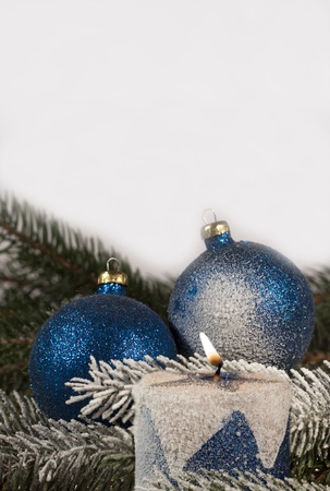 Christmas decoration, blue christmas balls and burning candle on spruce branch photo