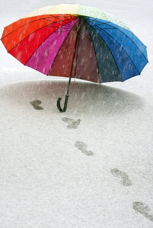 snow ground: Colorful umbrella in the fresh snow with some footprints around it.