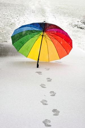 Kleurrijke paraplu in de verse sneeuw met sommige footprints eromheen.