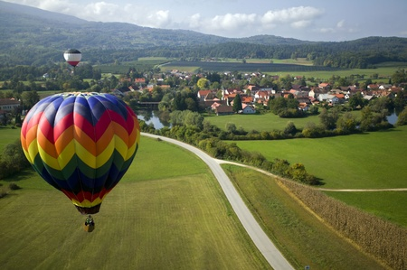 Flying over the fields and village in hot air balloons.