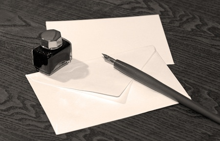 pad and pen: Old wooden ink pen on wooden table with blank letter.