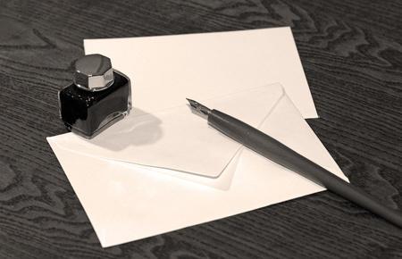 Oude houten inkt pen op houten tafel met lege brief. Stockfoto