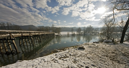 Winter landscape by the river with wooden bridge. Stock Photo - 8961142