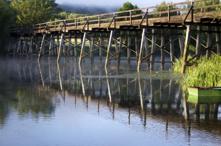 Old wooden bridge with reflections in the morning light. photo