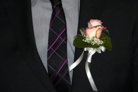 Closeup of the grooms suit with rose.