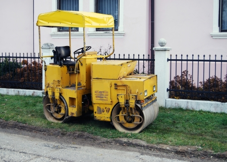 Old yellow steamroller by the road. photo