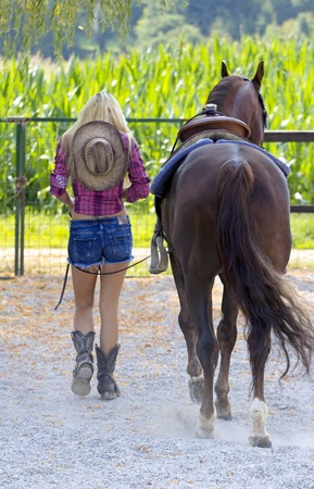 Beautiful blond woman walking with her horse.