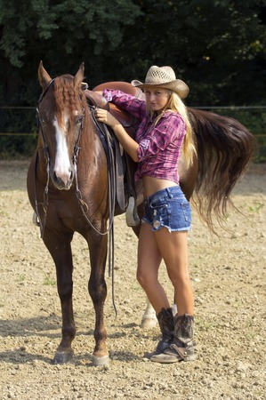 Beautiful blond cowgirl redy to ride a horse.