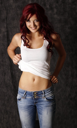 Sexy redhair girl in jeans and white top. Stock Photo