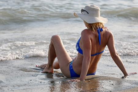 Blonde vrouw genieten van de zee op het zand strand.