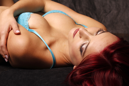 sexy redhead: Sexy redhead lying on her back in blue lace bra.