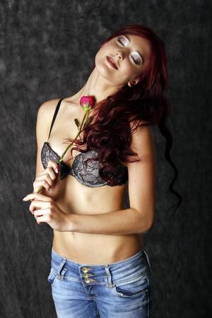 Mooie vrouw streelt zichzelf met rode roos.