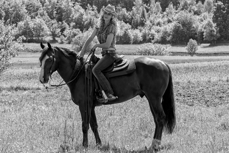 Mooie sexy cowgirl zittend op een paard.