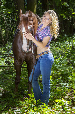 horse blonde: Sexy blonde cowgirl holding her horse in the forest.