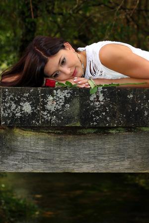Mooie brunette dagdromen in het park met rode roos naast haar.